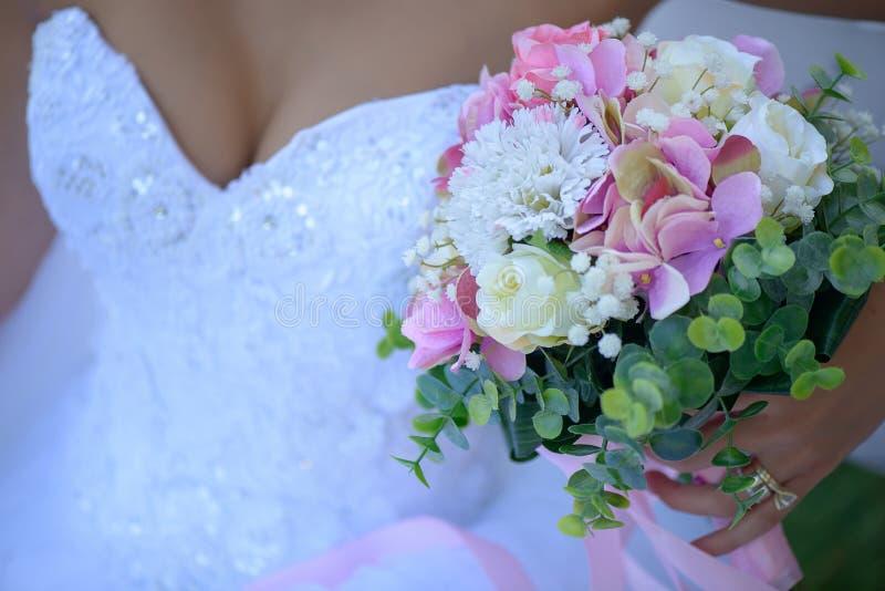 Braut, die empfindlichen Blumenblumenstrauß ein wesentlicher Zusatz für eine weiße Hochzeit hält lizenzfreie stockbilder