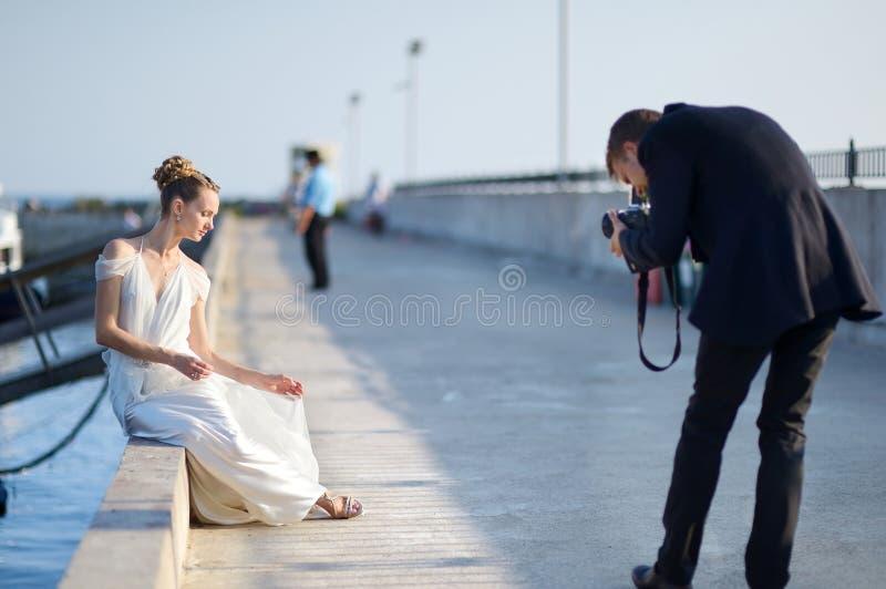Braut, die für ihren Bräutigam aufwirft lizenzfreie stockfotografie
