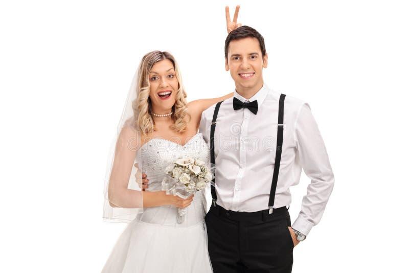 Braut, die Häschenohren auf dem Bräutigam herstellt lizenzfreie stockfotos