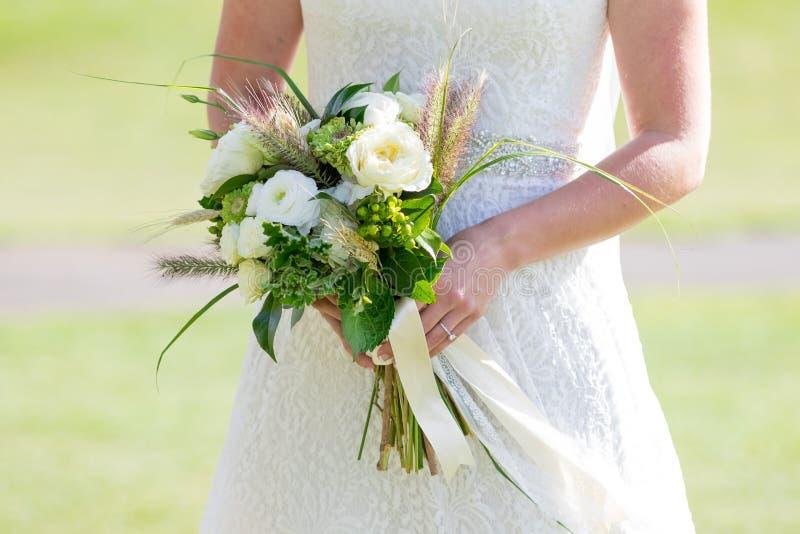 Braut, die Hochzeitsblumenstrauß hält stockbild