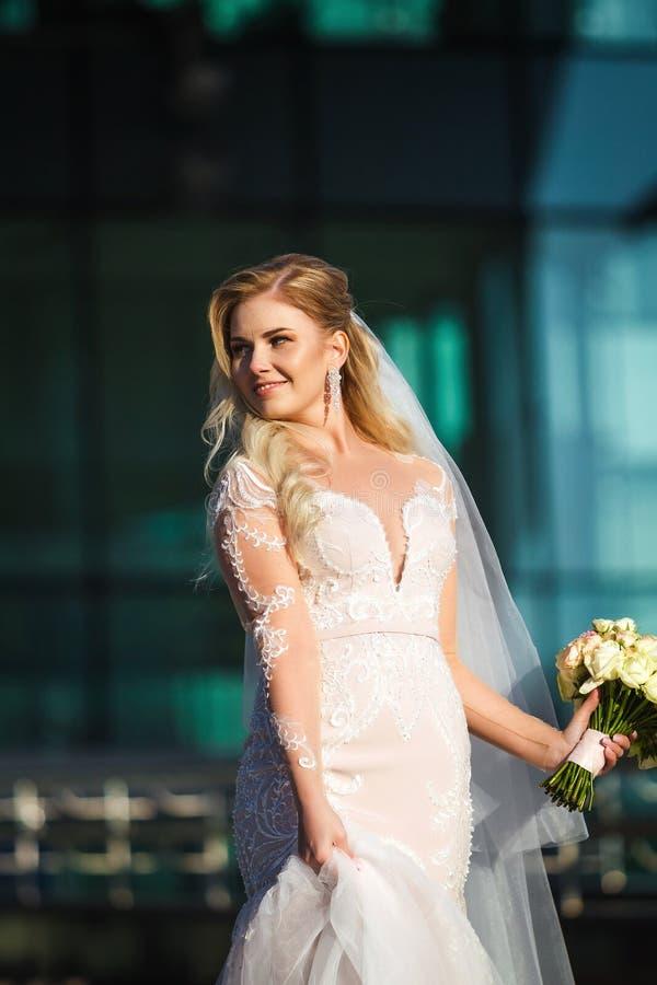 Braut, die ihr Kleid hält und Blumenstrauß heiratet stockfoto