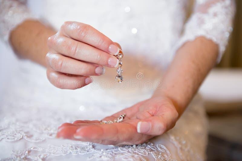 Braut, die ihre silbernen Ohrringe hält stockfotografie