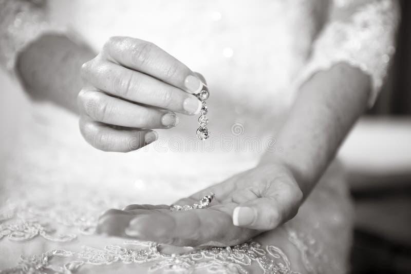 Braut, die ihre silbernen Ohrringe hält stockfotos