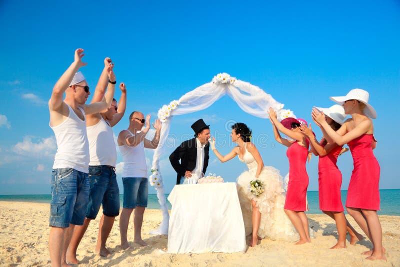 Braut, die ihrem Bräutigam einen Bissen des Hochzeitskuchens gibt. lizenzfreies stockbild