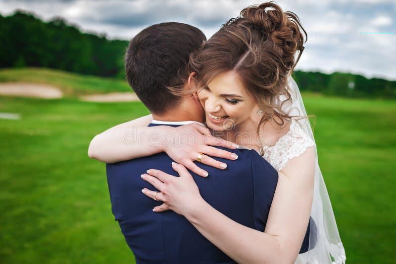 Braut, die ihren Bräutigam umarmt und in der Natur lächelt lizenzfreie stockfotografie