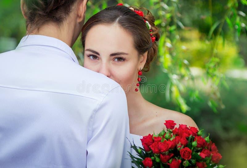 Braut, die ihren Bräutigam umfasst stockbild