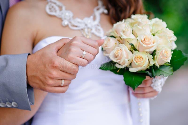 Braut, die mit Bräutigam in den Händen eines schönen Hochzeit bou geht lizenzfreie stockfotografie