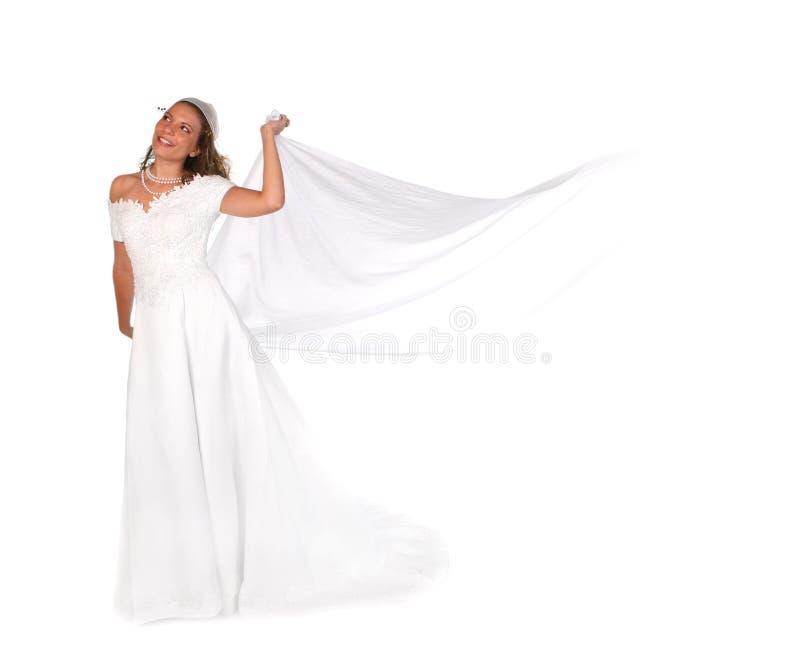 Braut, die oben schauen und wegholding-Schleier lizenzfreie stockfotografie