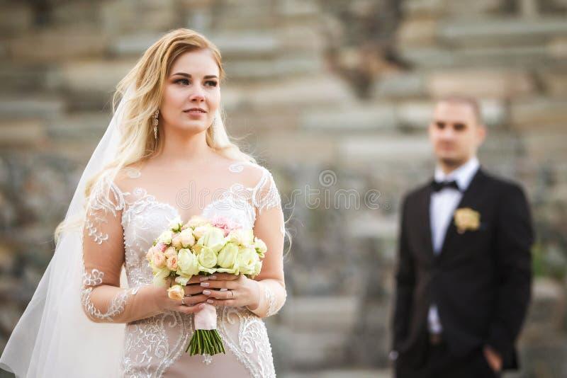 Braut, die schönen Hochzeitsblumenstrauß halten und Bräutigam, der hinten steht stockfotografie