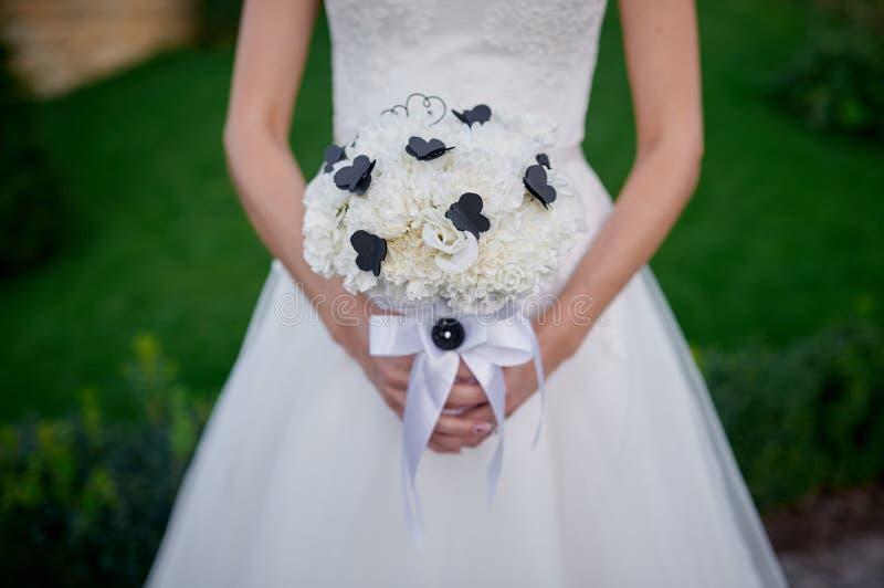 Braut, die schönen weißen Hochzeitsblumenstrauß in den Händen hält stockfoto