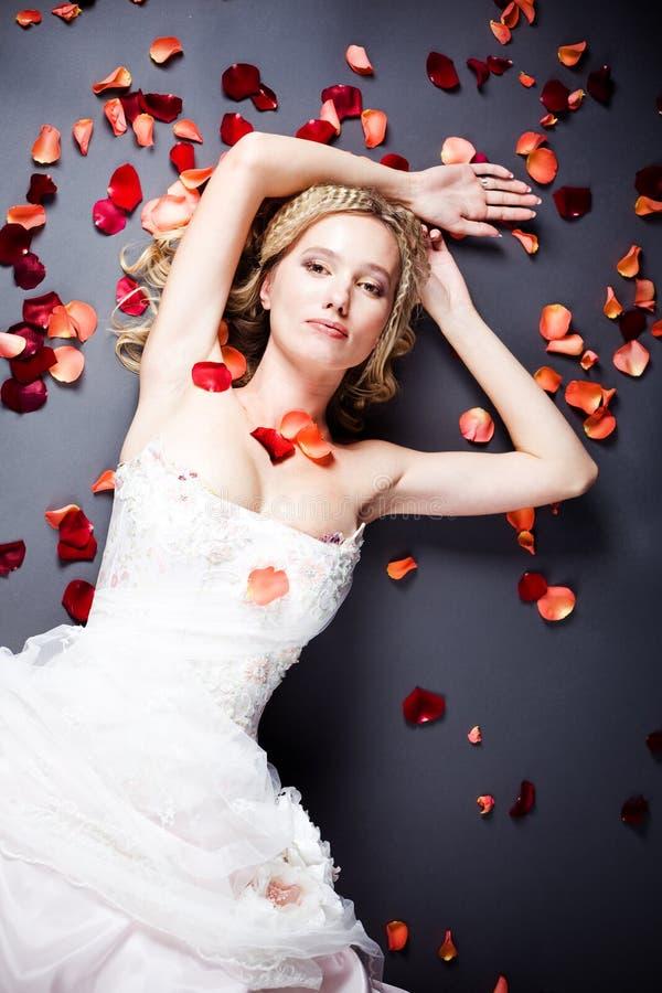 Braut, die unter rosafarbenen Blumenblättern liegt stockbild
