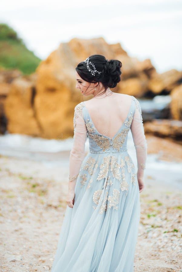 Braut in einem Blaulichtkleid gehend entlang den Ozeanstrand lizenzfreie stockfotografie