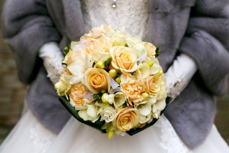 Braut in einem grauen Pelzmantel, der einen Brautblumenstrauß von Rosen hält Braut und Bräutigam draußen stockbild