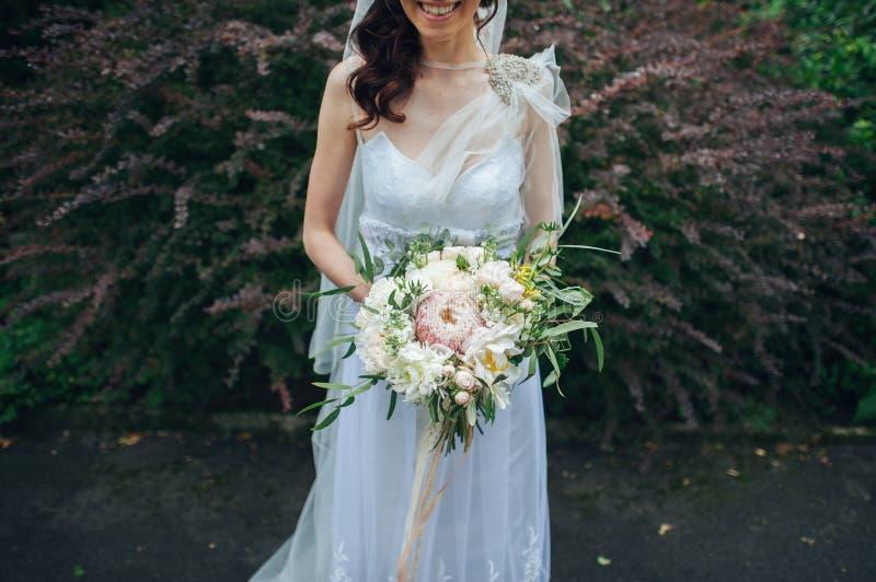 Braut in einem Kleid, das in einem grünen Garten steht und ein weddin hält lizenzfreie stockbilder