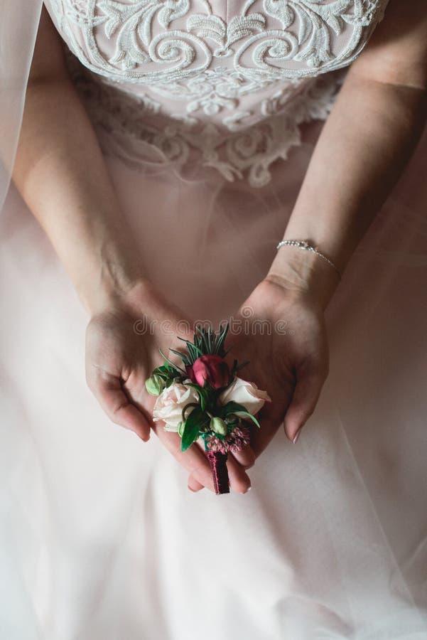 Braut in einem luxuriösen Hochzeitskleid, das ein Hochzeitsknopfloch gemacht von den Rosen hält stockfoto