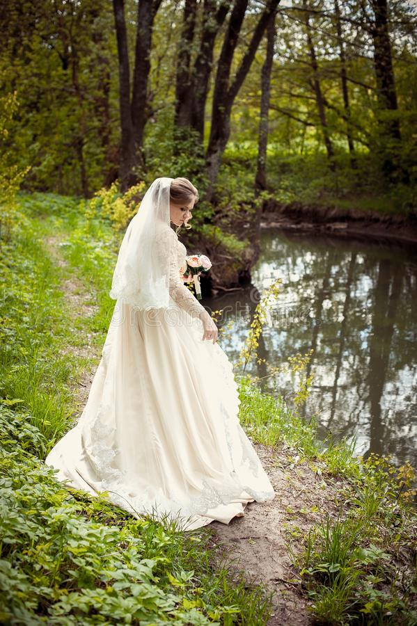 Braut in einem weißen Kleid auf dem Hintergrund der Natur Hochzeitsphotographie lizenzfreies stockfoto