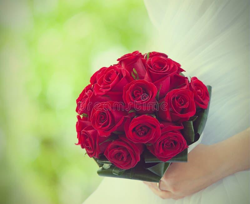 Braut hält Blumenstrauß von roten Rosen stockbilder