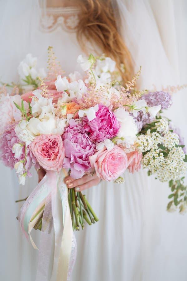 Braut hält Hochzeitsblumenstrauß lizenzfreie stockbilder