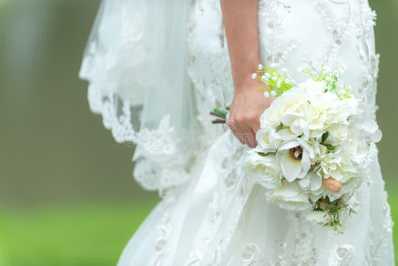 Braut h?lt einen Hochzeitsblumenstrau? an Heiratendes wei?es Kleid der Braut im Garten lizenzfreies stockfoto