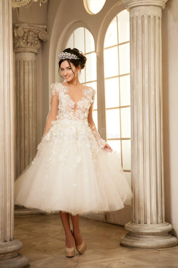 Braut hochzeit Die Braut in einem kurzen Kleid mit Spitze in der Krähe lizenzfreie stockfotografie