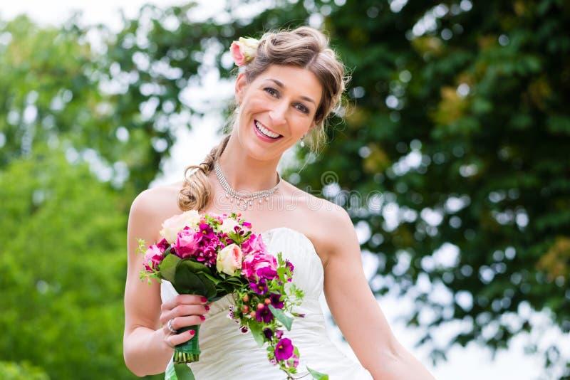 Braut im Hochzeits-Kleid mit Brautblumenstrauß lizenzfreie stockfotos