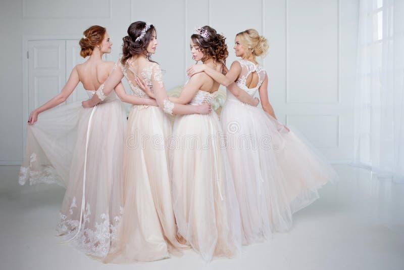 Braut im Hochzeitssalon Sind schönes Mädchen vier in einander ` s Arme Rückseite, Nahaufnahmespitzeröcke lizenzfreie stockfotos