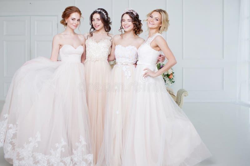 Braut im Hochzeitssalon Sind schönes Mädchen vier in einander ` s Arme Rückseite, Nahaufnahmespitzeröcke stockfoto