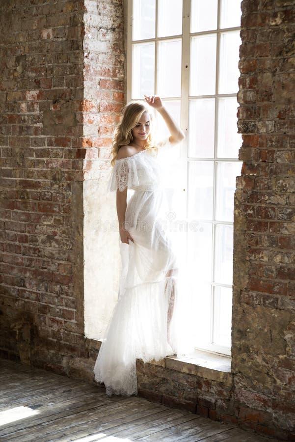 Braut im schönen weißen Kleid, das gegen das Fenster aufwirft stockfotografie