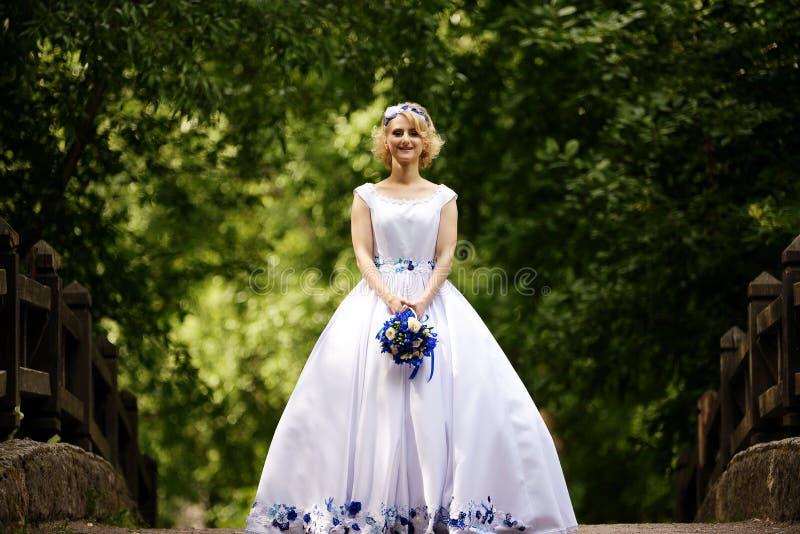 Braut im Schönheitshochzeitskleid, das auf Brücke steht stockfoto