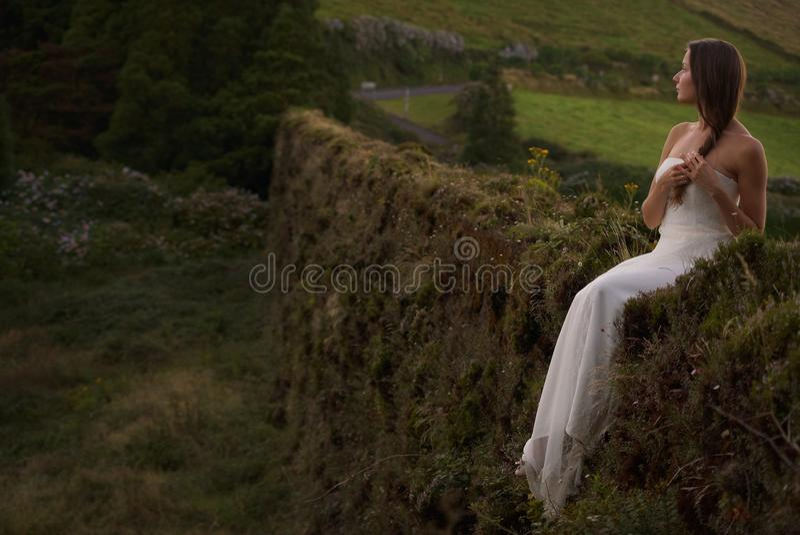 Braut im weißen Hochzeitskleid, das auf grasartigem altem brickwall auf Sao-Miguel-Insel, Azoren sitzt stockbild