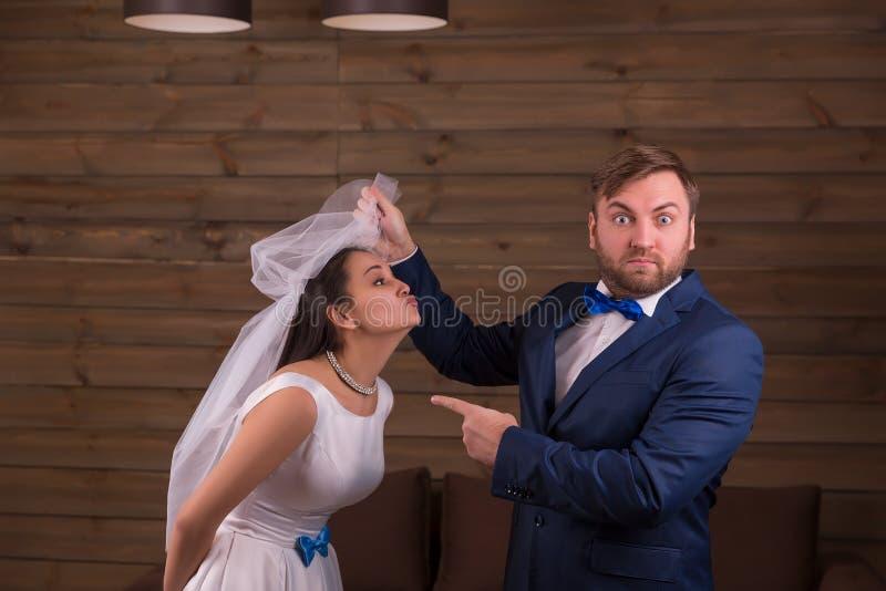Braut im weißen Kleid gegen überraschten Bräutigam lizenzfreies stockfoto