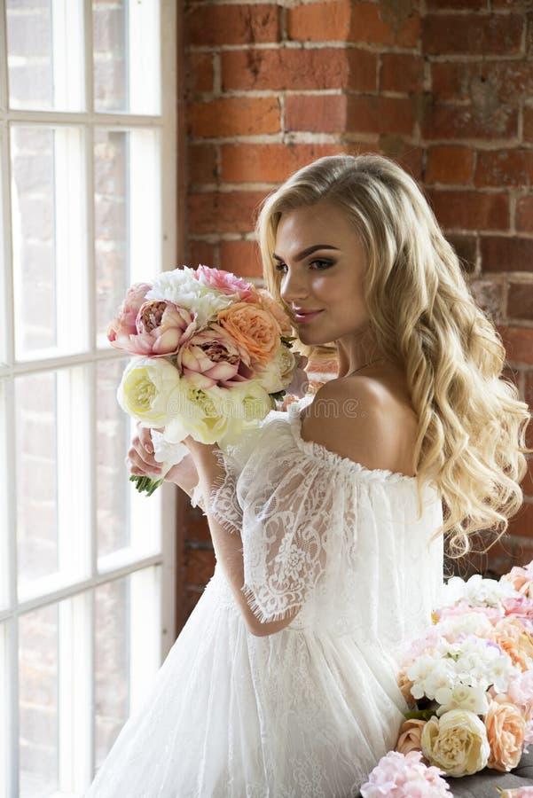 Braut im weißen Kleid mit dem gelockten Haar den Blumenstrauß schnüffelnd stockfotografie