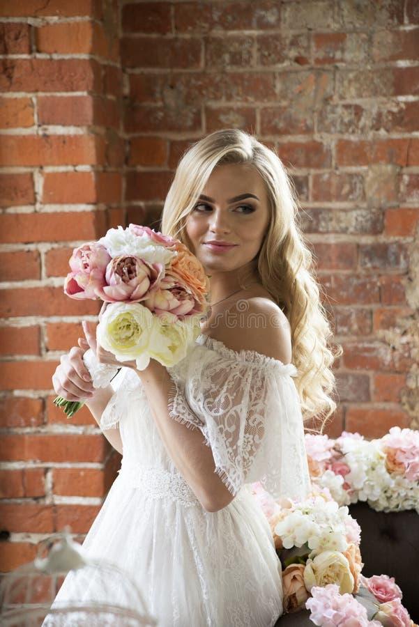 Braut im weißen Kleid mit dem gelockten Haar den Blumenstrauß schnüffelnd stockfotos