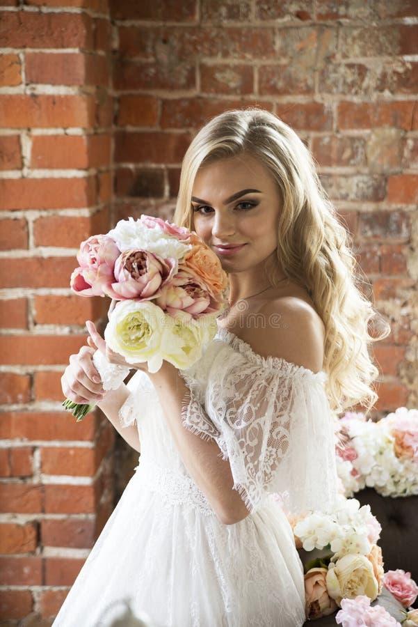 Braut im weißen Kleid mit dem gelockten Haar den Blumenstrauß schnüffelnd lizenzfreies stockfoto