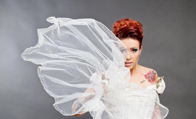 Braut im weißen Kleid mit Schleier
