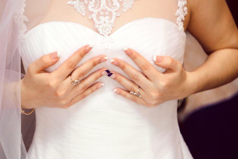 Braut im weißen Kleid stützt die Brüste mit den Händen stockfoto