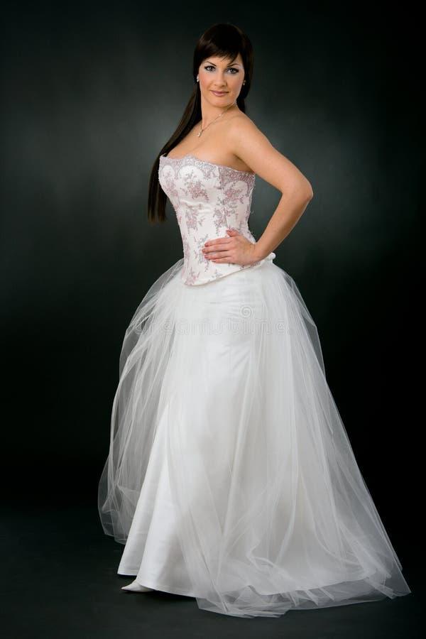 Braut innen mit Hochzeitskleid stockbild