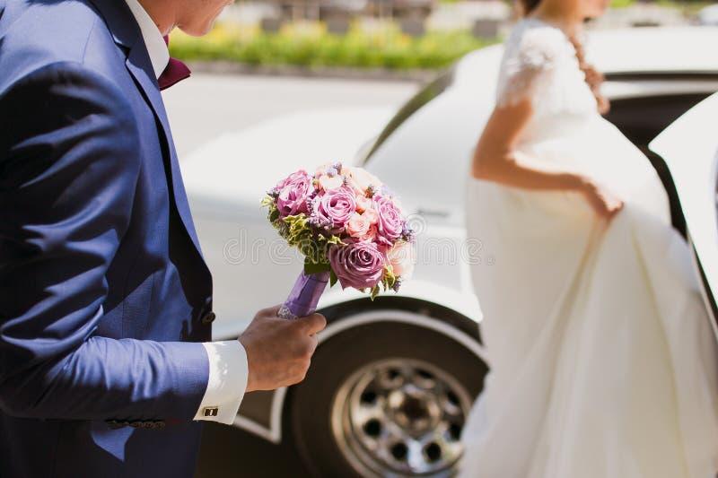 Braut kommt in das Auto lizenzfreie stockfotos