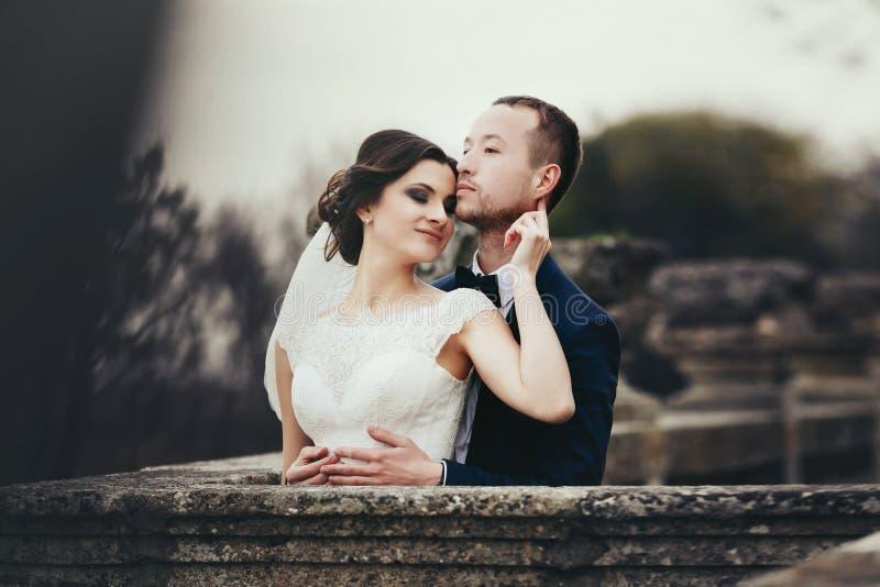 Braut lehnt sich, um ` s Kinn zu pflegen, das mit ihm auf dem alten Balkon steht lizenzfreie stockbilder
