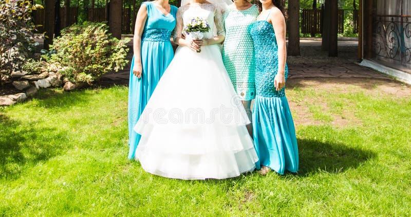 Braut mit Brautjungfern auf dem Park im Hochzeitstag stockfotografie
