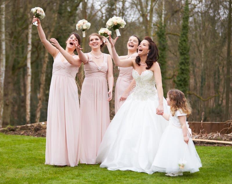 Braut mit Brautjungfern am Hochzeitstag lizenzfreie stockbilder