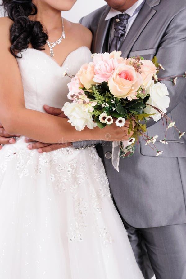 Braut mit dem Bräutigam, der Hochzeitsblumenstrauß an der Zeremonie hält stockfoto