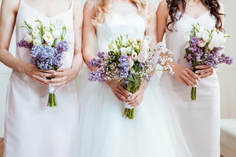 Braut mit den Brautjungfern, die Blumensträuße halten lizenzfreies stockfoto
