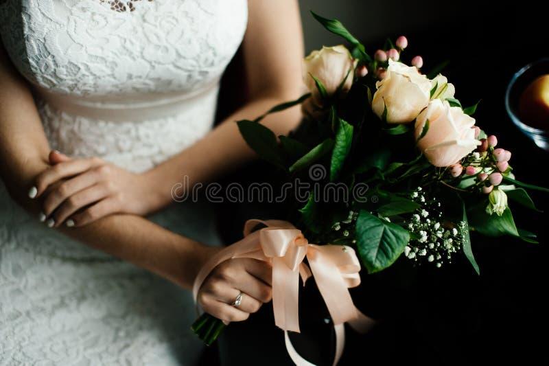 Braut mit einem Blumenstrauß von weißen Rosen sitzt durch die Tabelle stockfoto