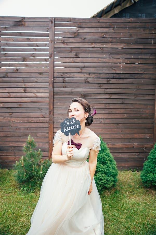 Braut mit einem Zeichen gerade geheiratet Süße Hochzeitsdetails über den Hochzeitstag Gleichheit, Krawatte und Kristallschmucksac lizenzfreies stockfoto
