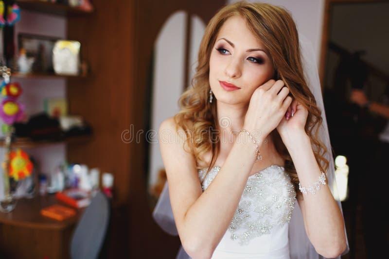 Braut mit erstaunlichem Make-up justiert sie jewerly in einem Raum stockfoto