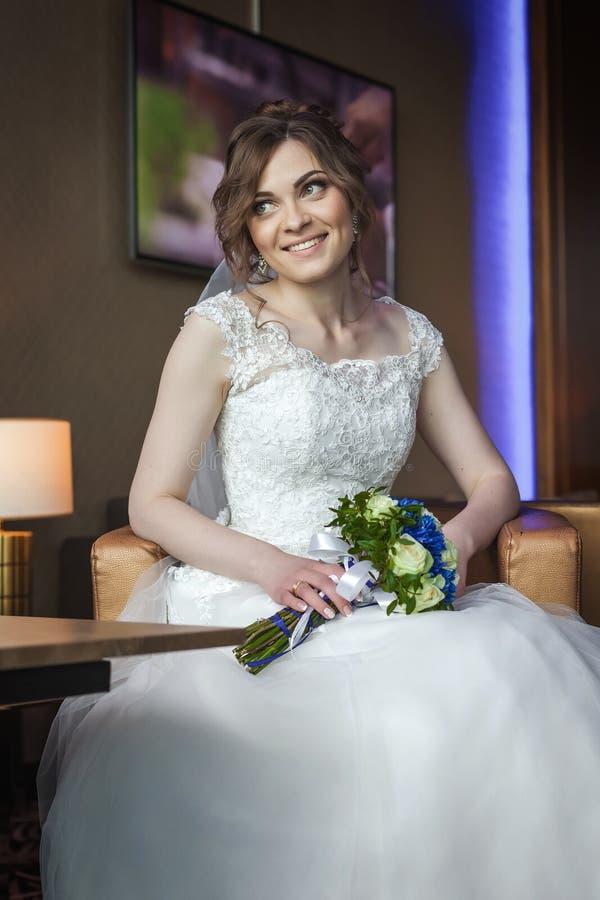 Braut mit Hochzeit blüht das Sitzen auf dem Lehnsessel und das Lächeln lizenzfreie stockfotos