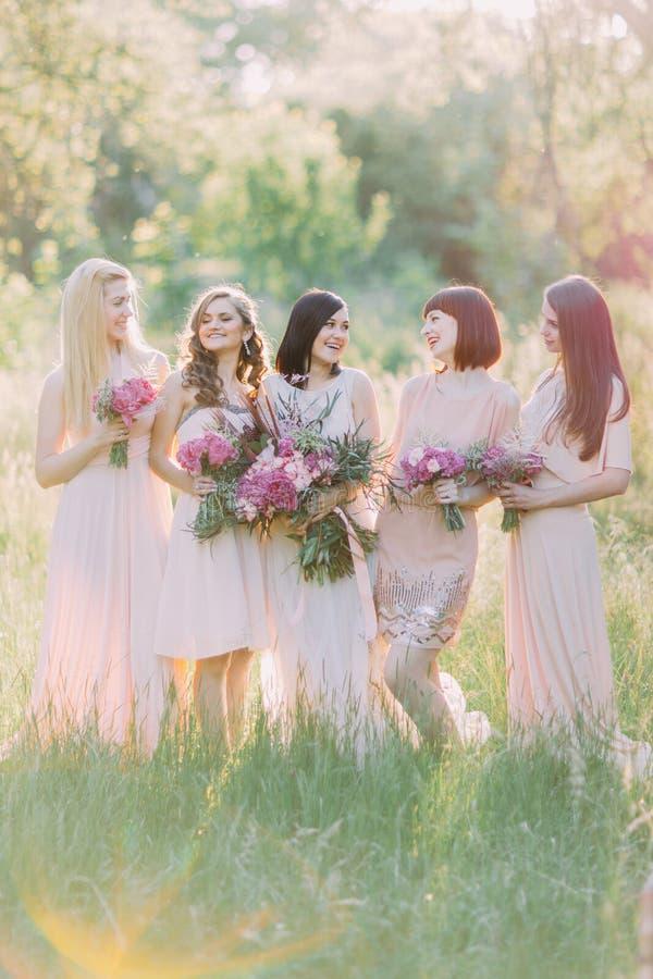 Braut mit ihren Brautjungfern sind, halten laughting und die Blumensträuße der rosa Blumen im grünen sonnigen Wald lizenzfreies stockbild