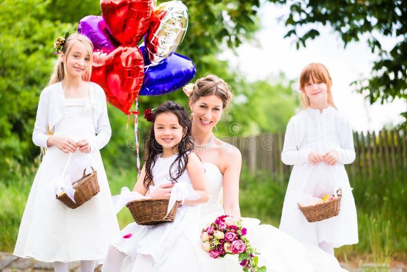 Braut mit Mädchen als Brautjungfern, Blumen und Ballonen lizenzfreies stockfoto