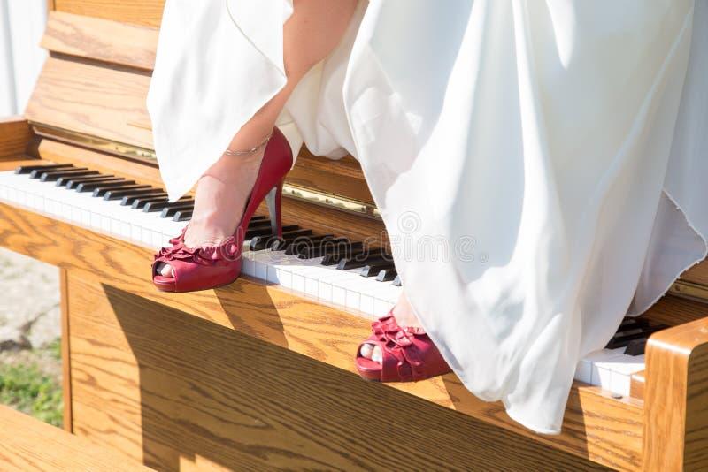 Braut mit roten Schuhen auf Klavier lizenzfreie stockbilder